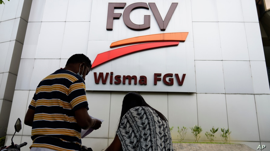 A couple talks outside FGV Holdings Berhad, one of Malaysia's largest palm oil companies, in Kuala Lumpur, Thursday, Oct. 1,…
