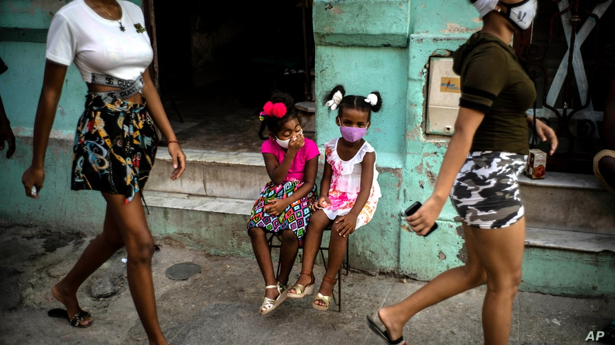 Wearing masks as a precaution against the spread of the new coronavirus Angelica Victoria, center left, and Thalia Oneida, wait…