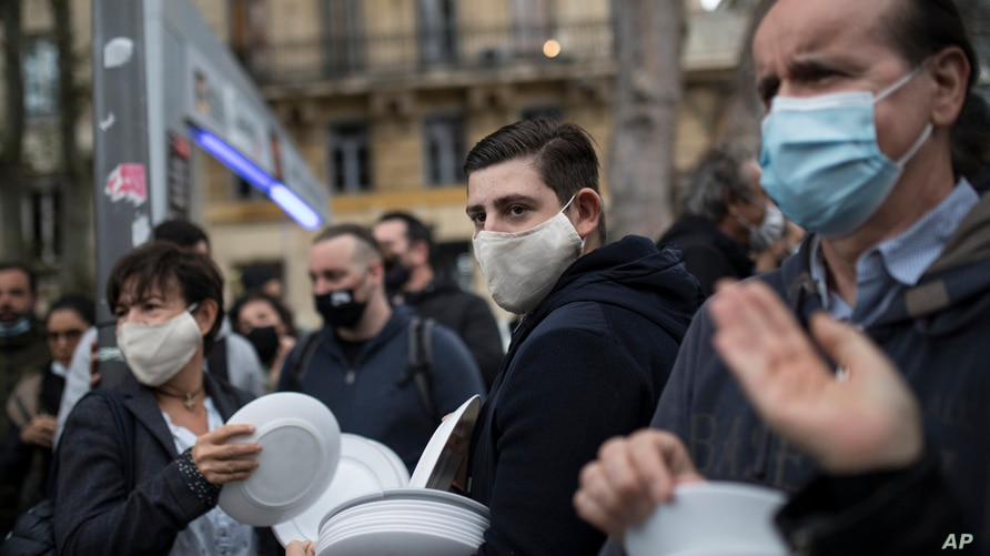 Restaurant and bar owners bang plates together and chant at a demonstration against restaurant and bar closures in Marseille,…