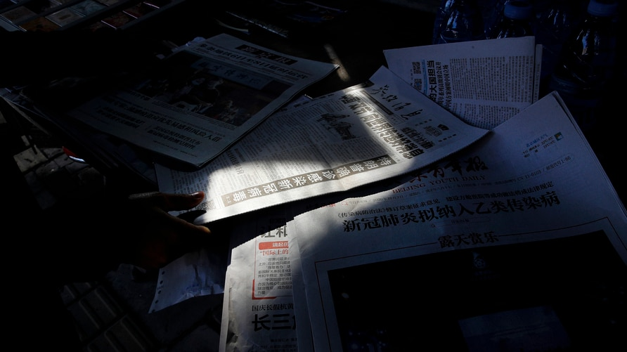 A woman arranges Chinese newspapers, as one of them with the headlines of President Donald Trump tested positive for the…