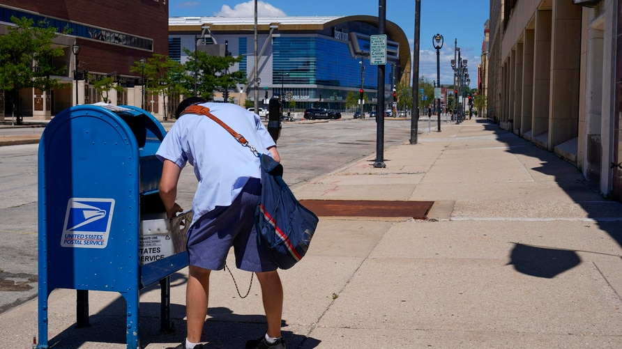FILE - In this Aug. 18, 2020, file photo, a postal worker empties a box near the Fiserv Forum in Milwaukee. U.S. Postal Service…