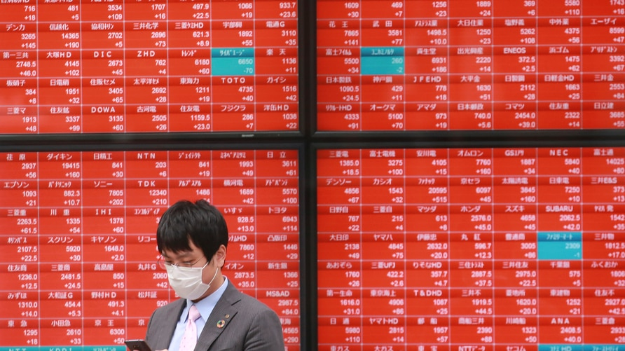 A man walks by an electronic stock board of a securities firm in Tokyo, Monday, Oct. 19, 2020. Shares advanced in Asia on…