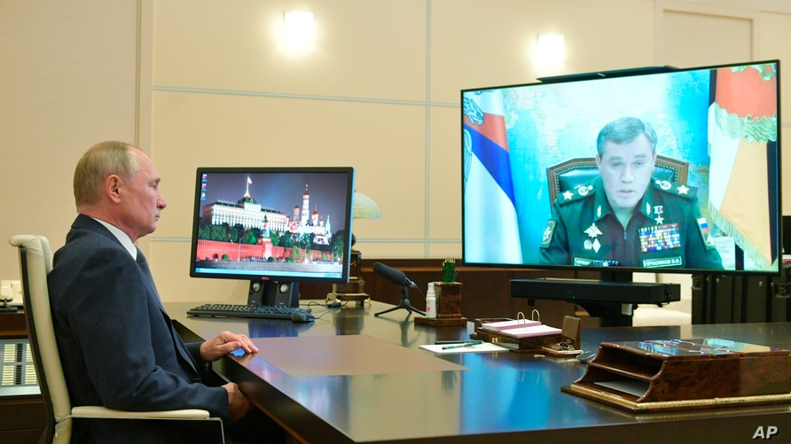Russian President Vladimir Putin listens to General Staff chief Valery Gerasimov, on the screen, during a video conference at…