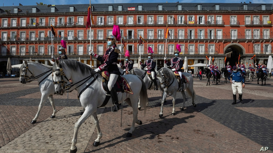 Members of the royal guard wearing face masks to prevent the spread of the coronavirus ride towards the foreign ministry in…