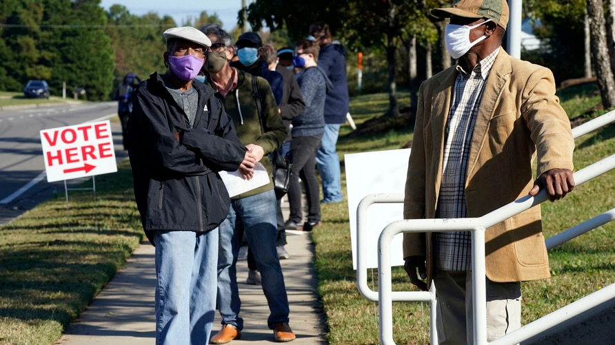 Early voters wait to cast their ballots at the South Regional Library polling location in Durham, N.C., Thursday, Oct. 15, 2020…