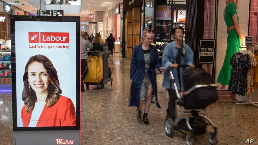 Shoppers walk past an electronic billboard showing a photo of New Zealand Prime Minister Jacinda Ardern in Christchurch, New…