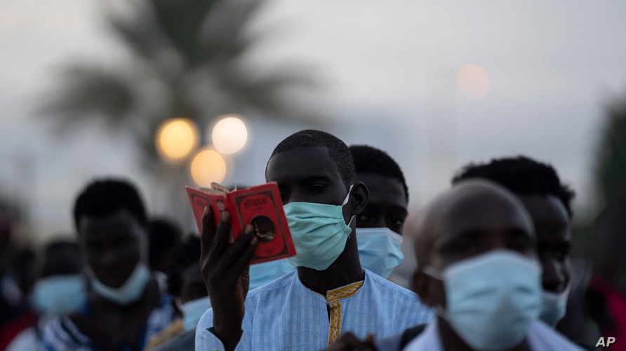 Wearing protective mask, a pilgrim from the Mouride Brotherhood, reads a book with poems written by Cheikh Amadou Bamba as he…