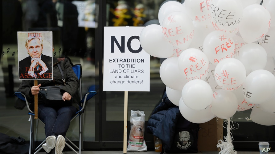 A demonstrator holds a banner as she sits near Free Assange balloons outside the Old Bailey in London, Thursday, Oct. 1, 2020,…