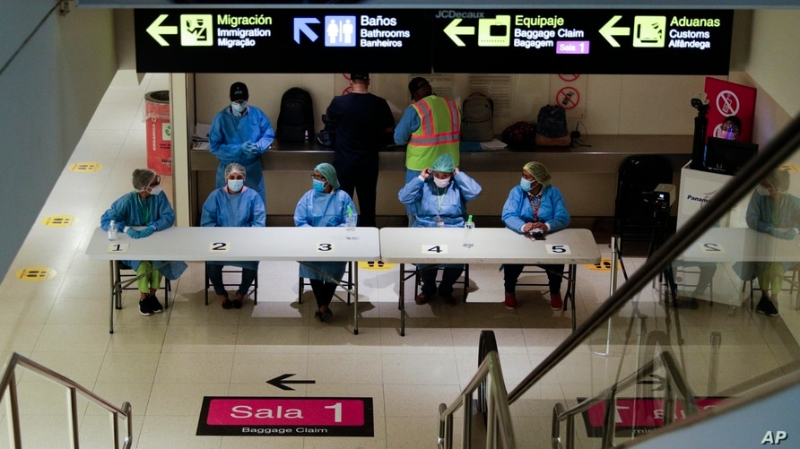 Health workers wait to revise arriving passengers' COVID-19 test results and administer tests to those who do not have one to…
