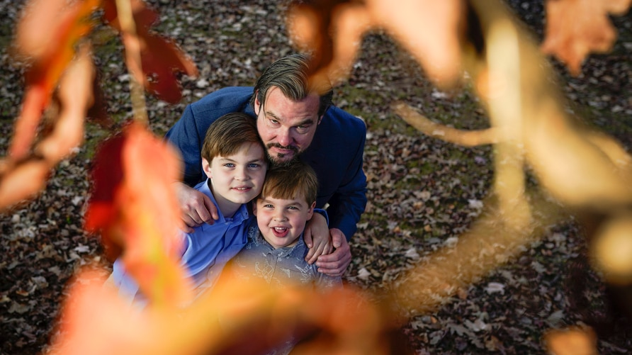 Christopher Hughey poses for a picture with his sons, Henry, 5, Harrison, 9, on Saturday, Nov. 21, 2020, in Charlotte, N.C…