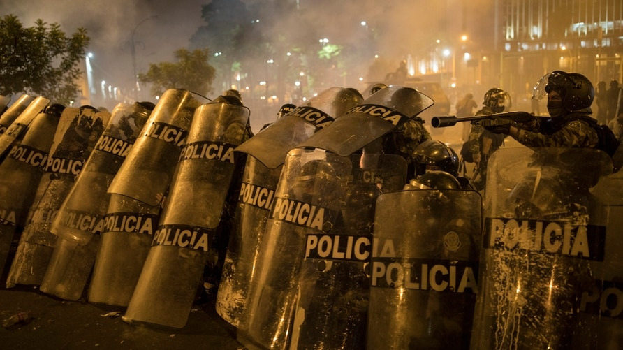 Police officers shield themselves from rocks thrown by protesters who were trying to march to Congress in a demonstration…