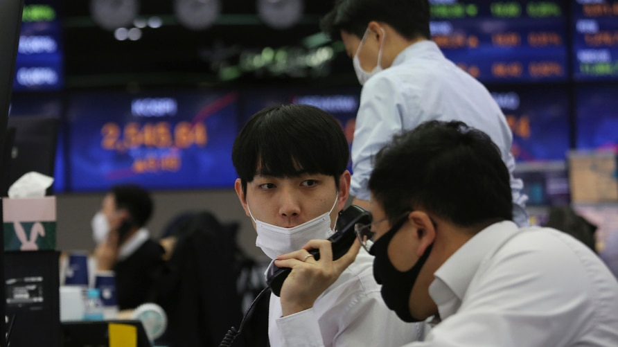 A currency trader talks with his colleague at the foreign exchange dealing room of the KEB Hana Bank headquarters in Seoul,…