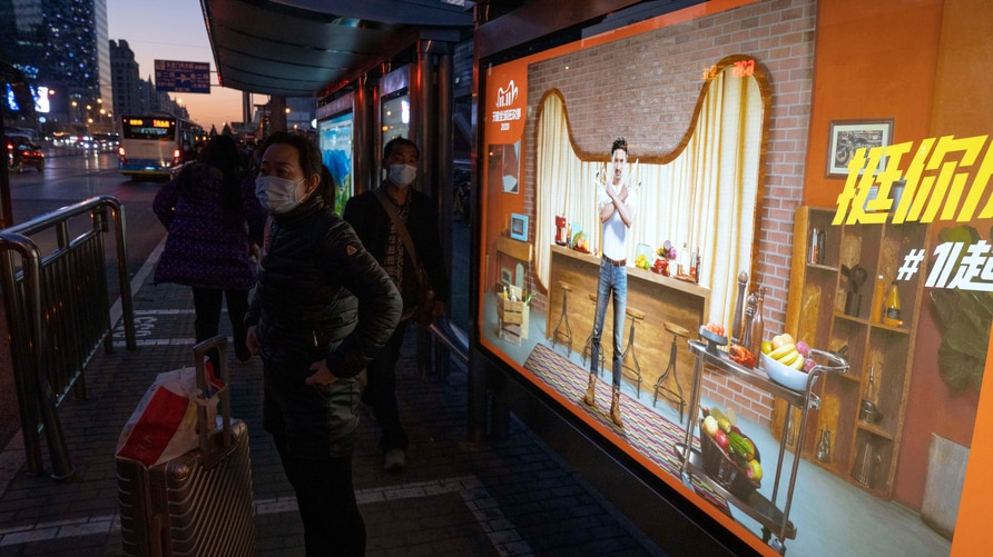 Residents wearing masks to protect from the coronavirus stand near an ad promoting the Nov. 11 Sales Day in Beijing on Sunday,…