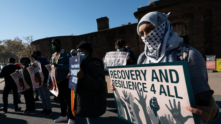 Yafa Dias holds a sign at an immigration reform rally, Monday, Nov. 9, 2020, in New York. Those at the rally are asking…