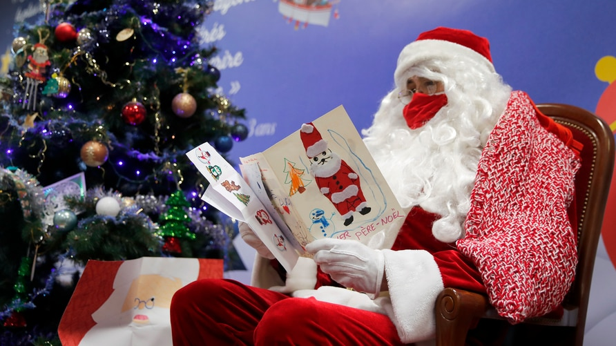 """FILE - In this Monday, Nov. 23, 2020 file photo, a postal worker dressed as Santa, reads letters to addressed to """"Pere Noel"""" -…"""