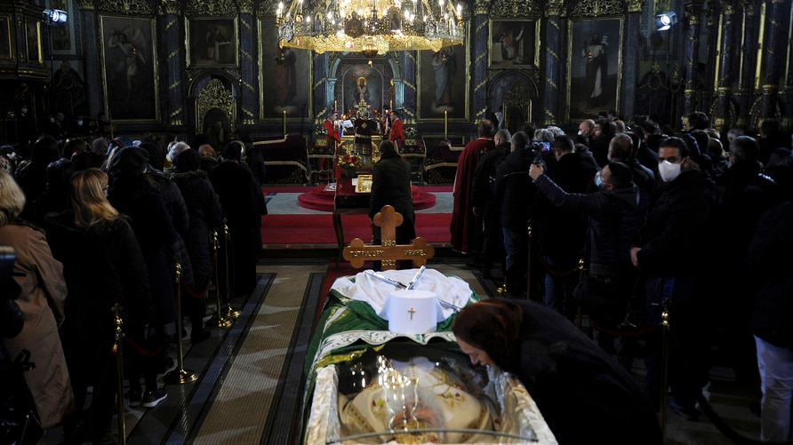 A woman kisses a protective screen over the coffin of Patriarch Irinej as he lies in repose at the Congregational church in…
