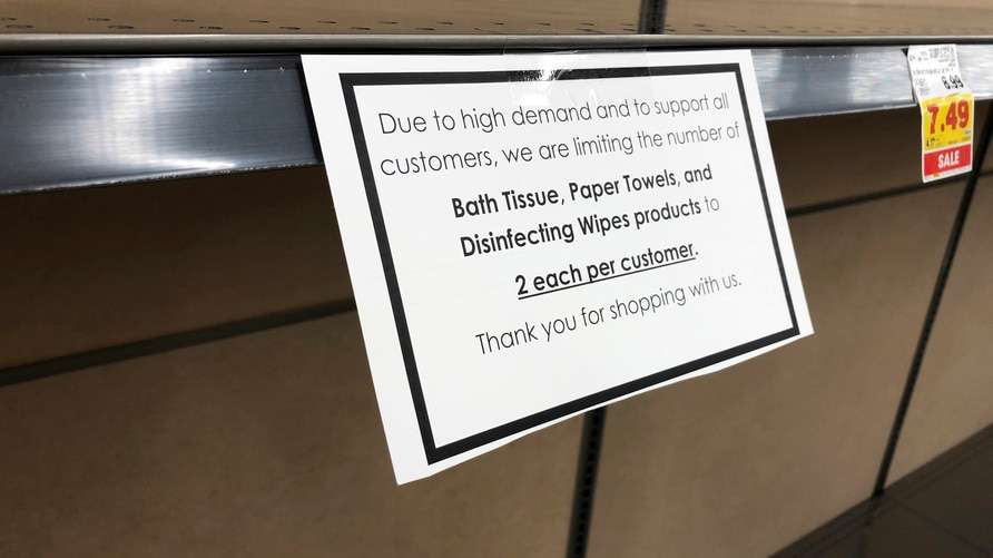 A sign to demote the limit on purchases of paper products hangs on the empty shelve of the paper aisle in a grocery store…