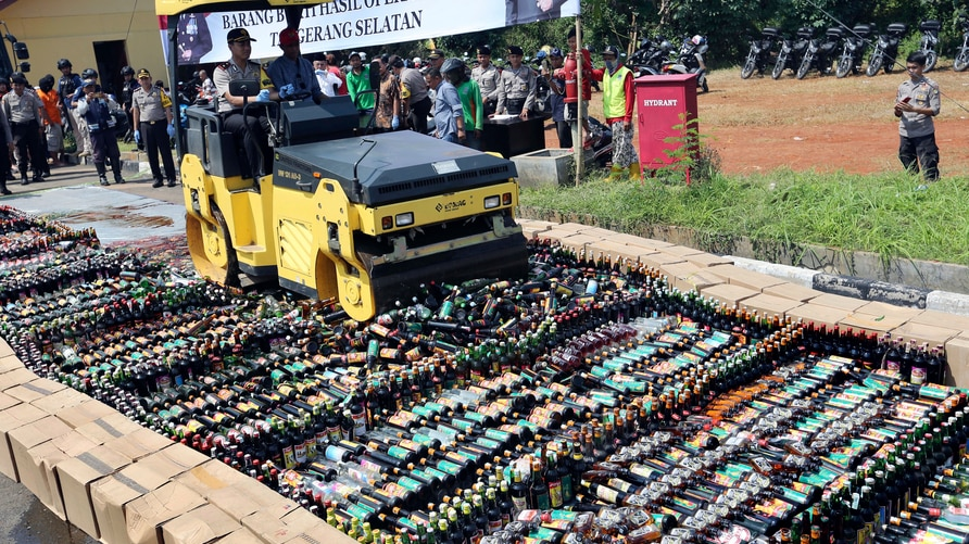 Police use a road roller to destroy bottles of illegal alcohol confiscated in Serpong, out of Jakarta, Indonesia. Friday, April…