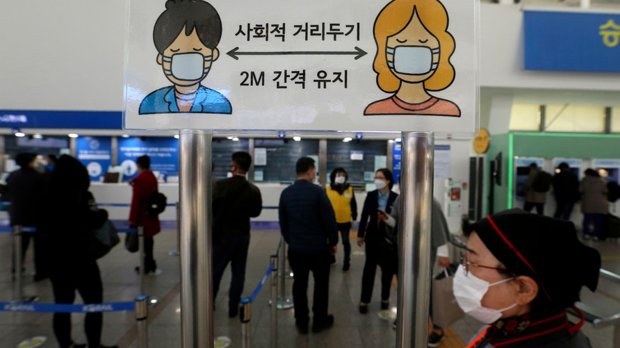 A social distancing sign is seen as people wait to buy tickets at the Seoul Railway Station in Seoul, South Korea, Friday, Nov…