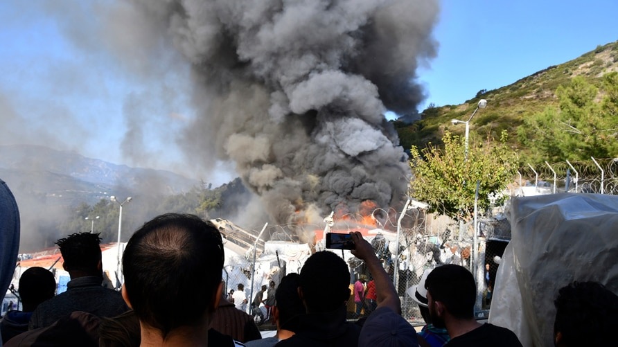 Migrants watch smoke rising from a fire inside a refugee camp on the eastern Aegean island of Samos, Greece, Wednesday, Nov. 11…
