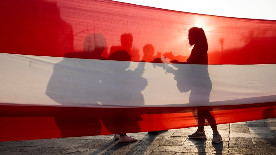 Demonstrators are silhouetted on a Peruvian flag before a march to demand significant social changes and a new constitution…