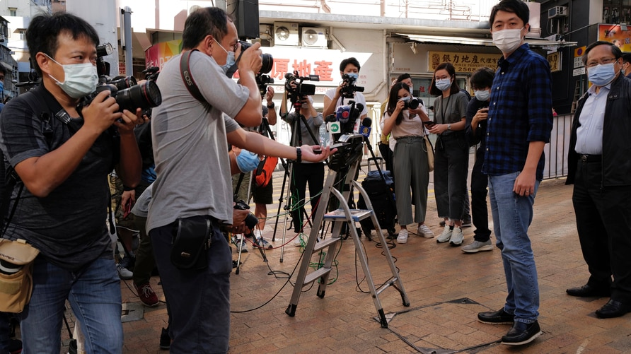 Pro-democracy legislator Ted Hui, second from right, is surrounded by photographers outside a police station after being…