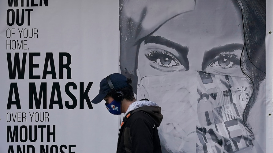 A pedestrian walks past a sign advising mask-wearing during the coronavirus outbreak in San Francisco, Saturday, Nov. 21, 2020…