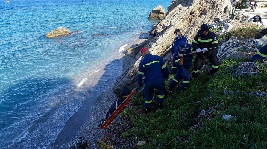 FILE - Firefighters retrieve the body of a migrant from the beach after a shipwreck on the island of Rhodes, southeastern Greece, Nov. 23, 2020.