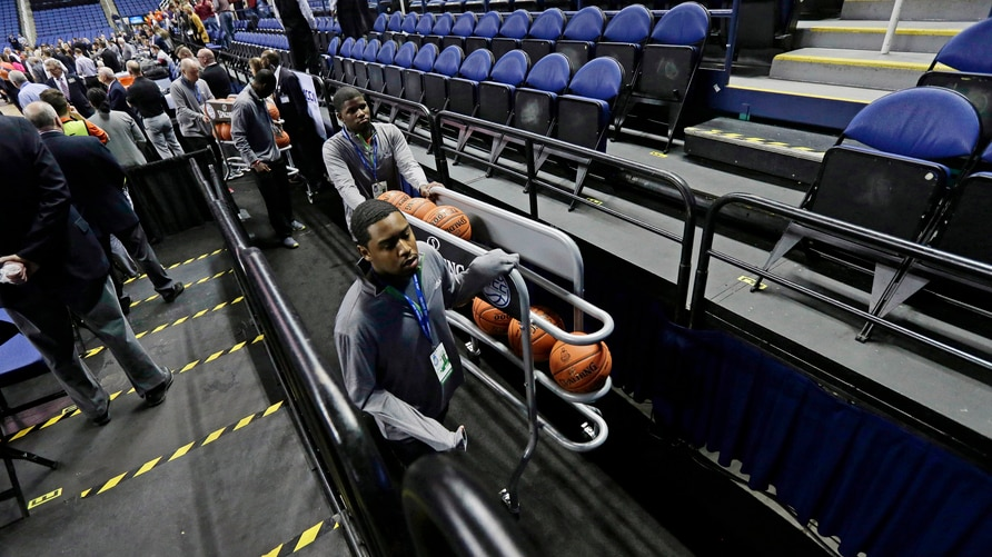 Personel remove the balls from the playing court after the NCAA college basketball games were cancelled at the Atlantic Coast…
