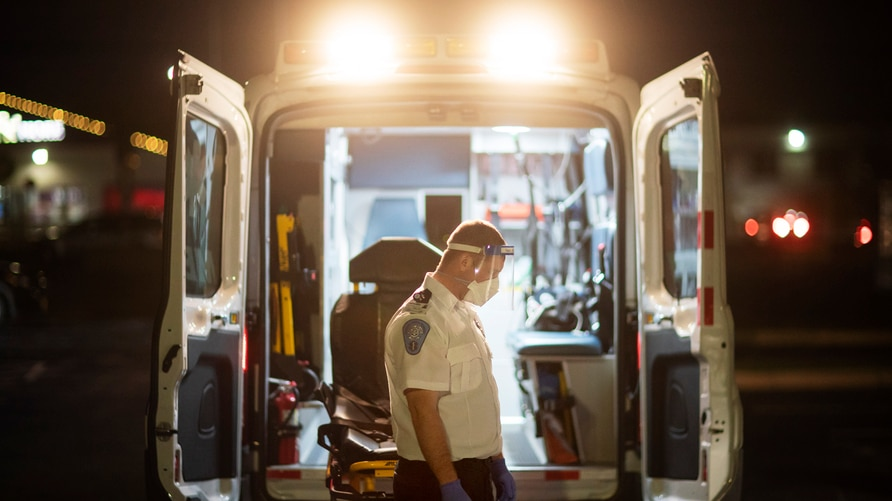 An EMT pauses for a moment while loading a stretcher back into an ambulance after dropping off a patient at a newly opened…