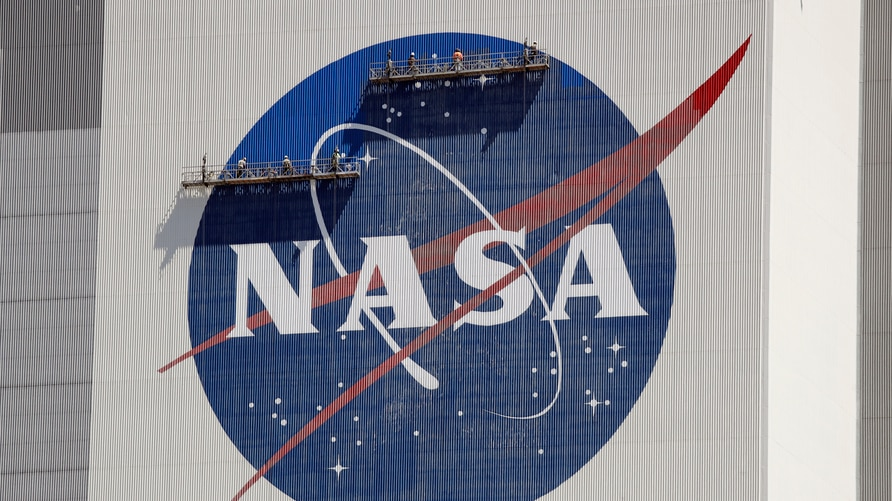 Workers near the top of the 526 ft. Vehicle Assembly Building at the Kennedy Space Center spruce up the NASA logo standing on…