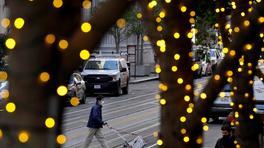 Holiday lights line trees as people wearing face masks cross an intersection during the coronavirus pandemic in San Francisco,…