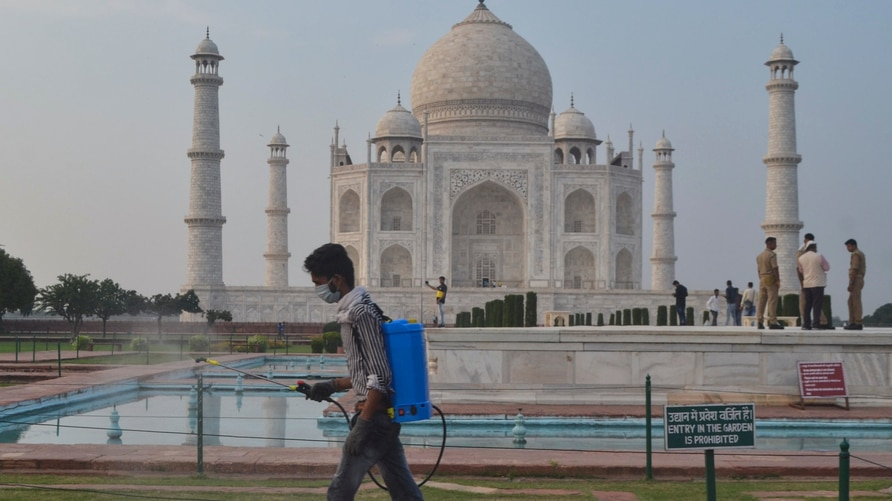 A man disinfects the premises of the Taj Mahal monument that was reopened after being closed for more than six months due to…