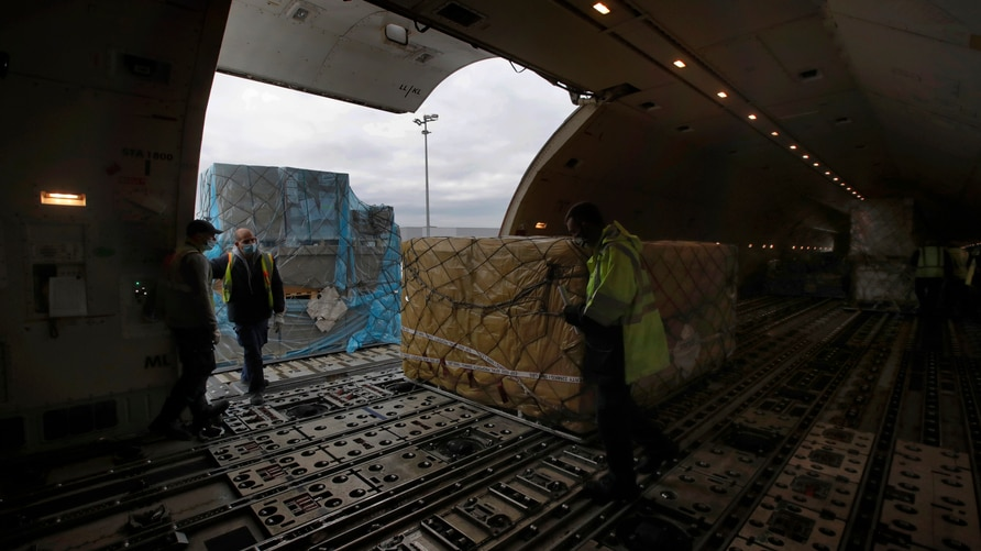 Air France cargo workers load equipments and pharmaceutical containers in a cargo plane at Roissy airport, outside Paris,…