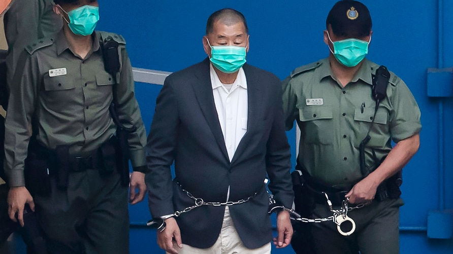FILE - In this Dec. 12, 2020, file photo, Jimmy Lai, center, who founded the Apple Daily tabloid, is escorted by Correctional…