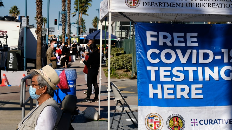 People wait in line to be tested for COVID-19 at a testing site in the North Hollywood section of Los Angeles on Saturday, Dec…