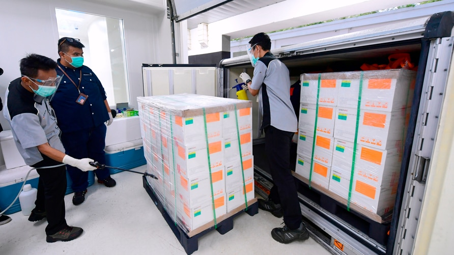 FILE - In this Dec. 7, 2020, file photo, released by Indonesian Presidential Palace, workers spray disinfectant on boxes…