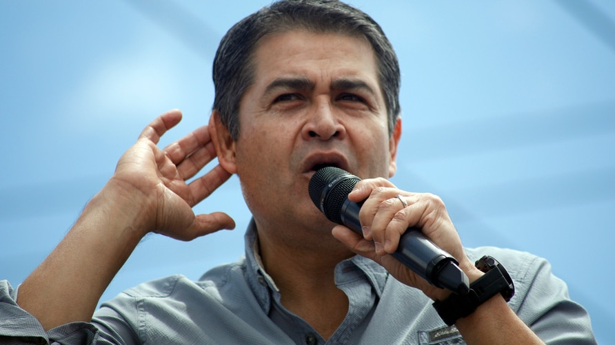 FILE - In this June 22, 2019 file photo, Honduras' President Juan Orlando Hernández listens to the crowd as he delivers his…