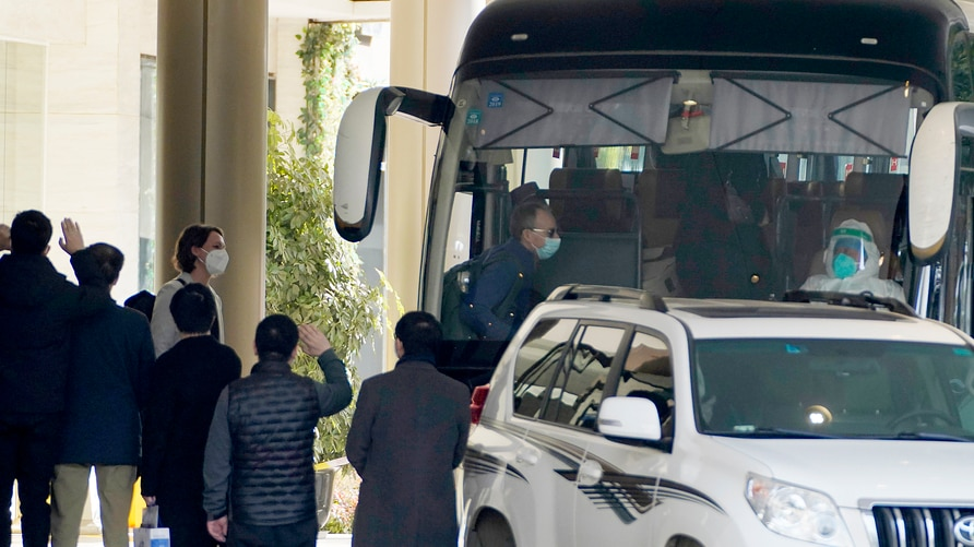 Workers wave to the team of experts from the World Health Organization who ended their quarantine and prepare to leave the…