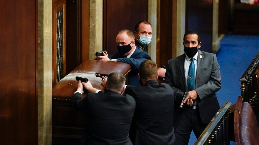 U.S. Capitol Police with guns drawn stand near a barricaded door as protesters try to break into the House Chamber at the U.S. Capitol, Jan. 6, 2021, in Washington.