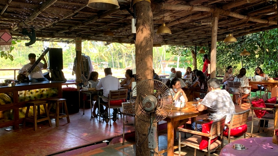 People sit at a restaurant at Anjuna in North Goa, India, Dec.12, 2020. Months after the lockdown began to ease, Goa is showing…