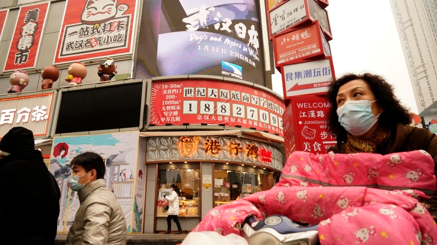 """Residents wearing masks past by a screen showing a trailer for the film """"Days and Nights in Wuhan"""" outside a mall in Wuhan in…"""