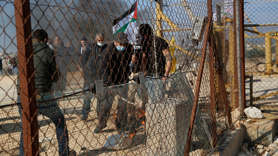 Palestinian demonstrators break a gate of the Israeli barrier during a protest against Israeli settlements in the outskirts of…