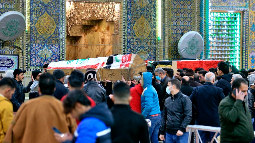 Mourners carry flag-draped coffins of suicide bomb victims at the Imam Ali shrine in Najaf, Iraq, Thursday, Jan. 21, 2021. Iraq…
