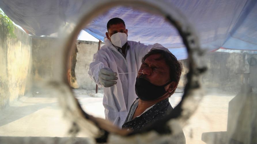 A health worker takes a nasal swab sample at a COVID-19 testing center in Hyderabad, India, Saturday, Jan. 2, 2021. India…