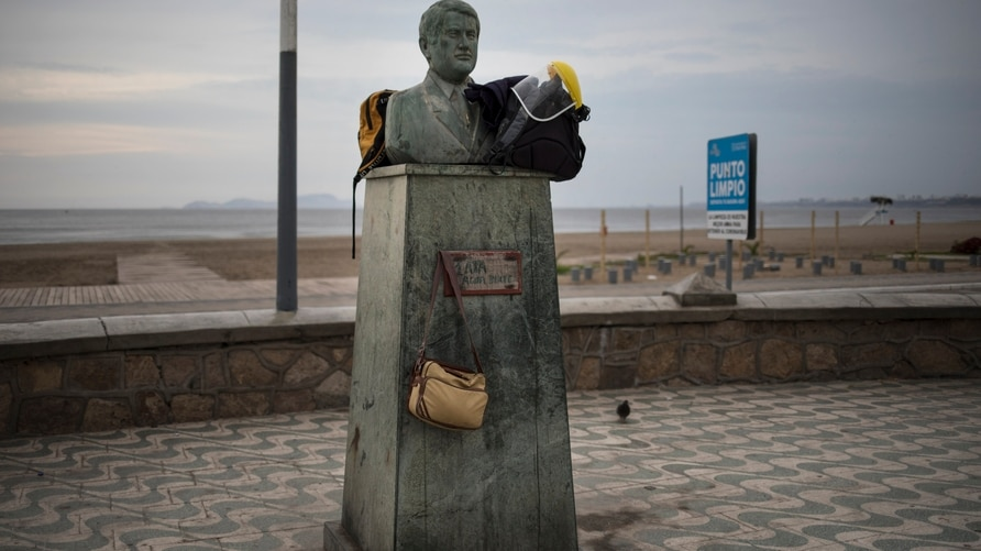 A face shield and a couple of backpacks sit on a bust on the beach amid the new coronavirus pandemic in Chorrillos, Lima, Peru,…