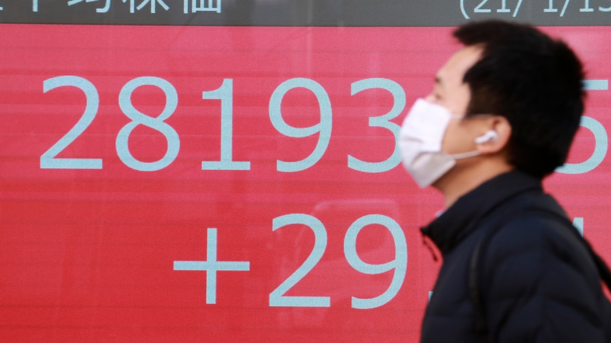 A man walks by an electronic stock board of a securities firm in Tokyo, Wednesday, Jan. 13, 2021. Asian stock markets were…