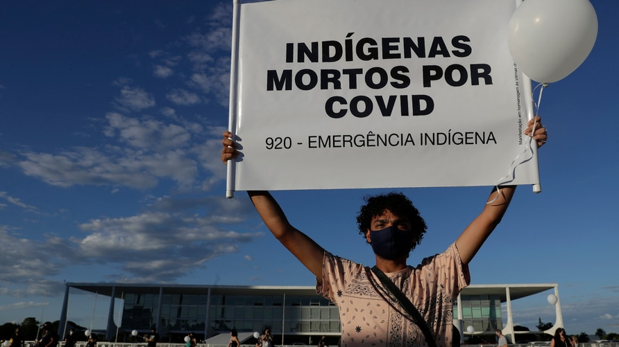 """A demonstrator shows a sign with text written in Portuguese that reads """"Indians Killed by Covid"""" during a protest against the…"""