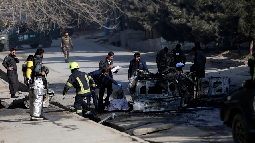 Afghan security officers inspect the site of a bombing attack in Kabul, Afghanistan, Sunday, Jan. 10, 2021. A roadside bomb…