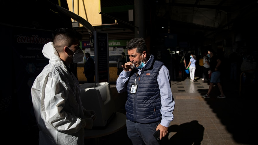 A man blows into a vial for a free, COVID-19 rapid test at a bus station for long-distance travelers in Santiago, Chile, Friday…